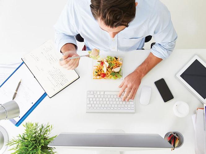 Vừa làm việc vừa ăn càng khiến bạn căng thẳng đầu óc. Ảnh minh họa: Shutter Stock