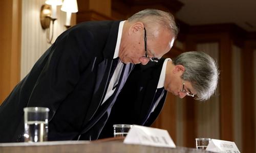 Cán bộ Đại học Y Tokyo cúi đầu xin lỗi tại cuộc họp báo ngày 7/8. Ảnh: AFP.